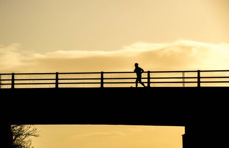 An adult male running across a motorway bridge while he tries to improve his health  fitness.