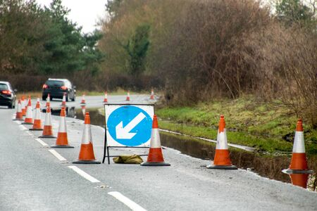 A main road through part of the United Kingdom is coned off to protect drivers from driving through a flooded lane.
