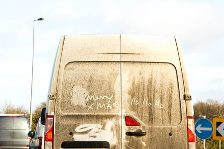 A white van that has had a festive message written in the dirt, on its back doors.