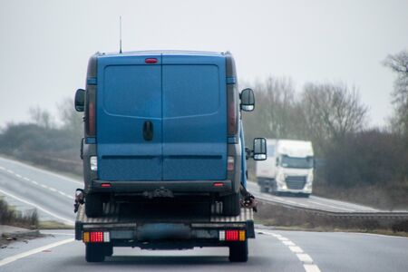 A blue breakdown vehicle carrying a blue van on the back. The view from behind.