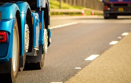 A closeup of wheels in motion from an articulated lorry, traveling along a UK motorway. Imagens