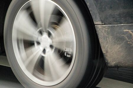 A close up of a vehicle wheel whilst it is in motion.