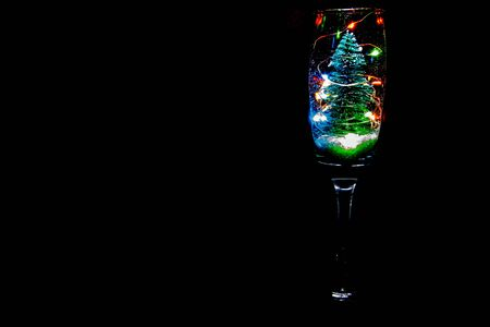 A champagne glass with a Christmas tree, lights and snow bringing that festive celebration.