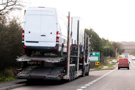 A large truck transporting new vehicles to its customer.