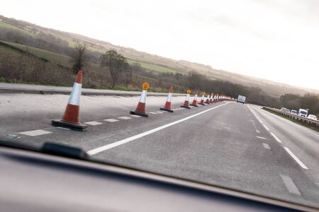 Road work cones controlling the lanes for traffic to keep them out of a works zone.