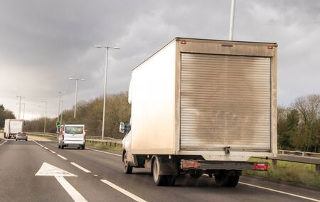 A white van traveling along a main road in the United Kingdom, the roads wet and dirty.