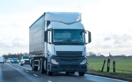 Een grote vrachtwagen rijdt door het land om goederen af te leveren of op te halen voor de volgende bedrijfslocatie.