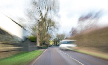 A view along a main road with motion blur showing the movement of traffic and the vehicle being driven.