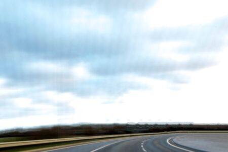 The perspective of a driver and  or passenger on a journey along a long road. Reklamní fotografie