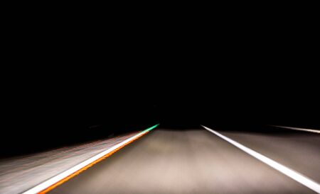 A driver or passengers view from their seat during a long journey at night.