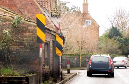 Yellow and black marker signs show warning to wider vehicles that they may strike the wall that pretrudes into the roadway.