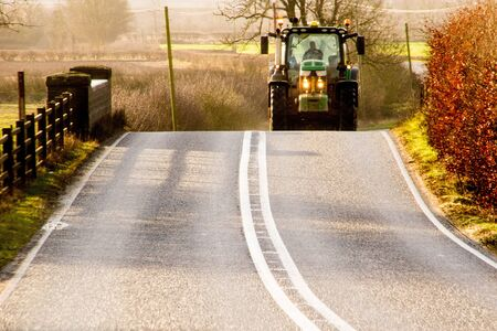 A farmer in his tractor oncoming on a main road.