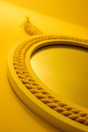 A circular mirror surrounded by a rope design, on a wall.