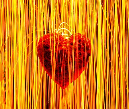 A large red heart which has clearly had long term damage to it through some type of illness. Sparks raining down on the heart. Stock Photo