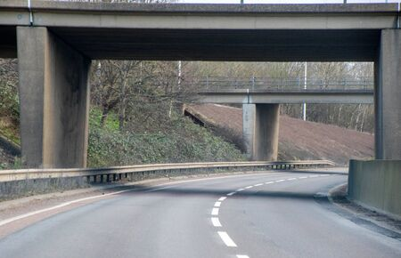 A typical British road leading under a small bridge. The road leading round to the right in the distance, being empty of other traffic. Stock Photo