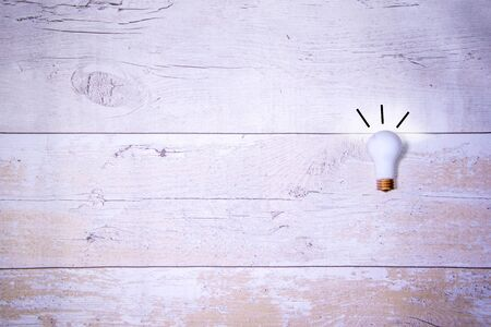 A single light bulb against a wood effect background. Giving the idea concept.
