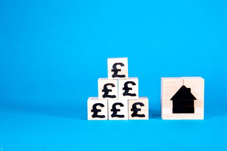 The cost of housing is a huge issue nationally and internationally. Here wooden blocks with symbols of currency show the rising costs of property investment or rent. Stock Photo