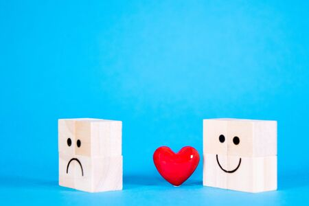 Wooden blocks with a happy face and a sad face, one giving a bright red heart to the other as an apology or make up gesture. Banco de Imagens