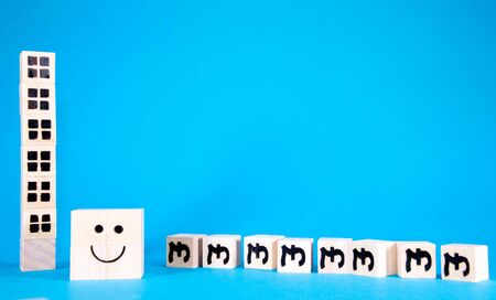 A happy face standing beside fallen price symbol blocks to symbolize the falling costs of property prices.