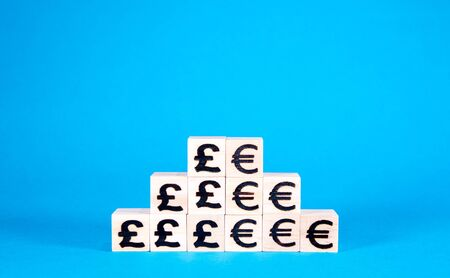 Pound and Euro currency symbols on wooden blocks stacked side by side.
