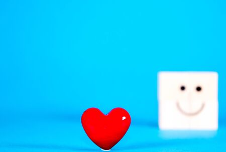 A wooden block standing beside a bright plush red heart as a gesture for Valentine's Day, on the 14th February. Stock Photo