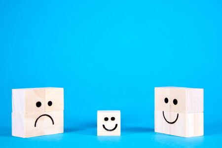 A family of faces with a mixture of emotions, large and small on wooden blocks, standing side by side. Banco de Imagens