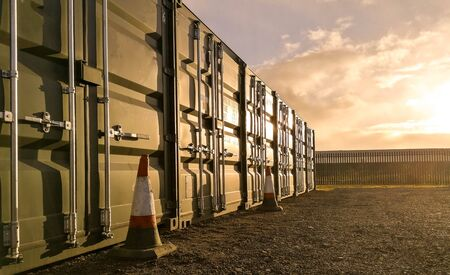 A row of storage containers with the sun setting in the background. Stock fotó