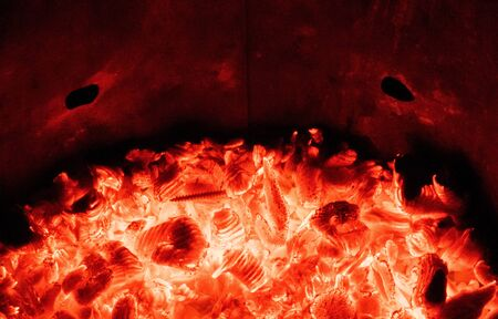 A look deep into a well lit fire. Orange, red and black emmitting due to the heat and flames of a garden waste bin fire.