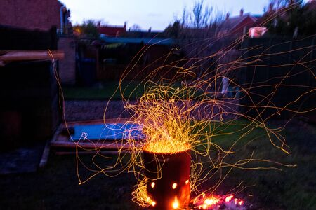 A look deep into a well lit fire. Orange, red and black emmitting due to the heat and flames of a garden waste bin fire. Stock Photo