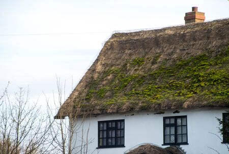 A very old method of roofing, and expensive, thatch roofing can keep your home warm but like this one can also get covered in moss.