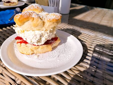 A delicious and mouth watering cream scone on a plate, in a sunlit cafe.