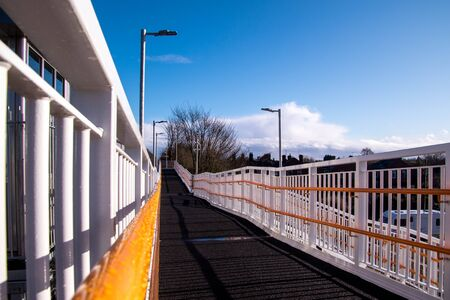 A view along a new train station platform during a sunny day.
