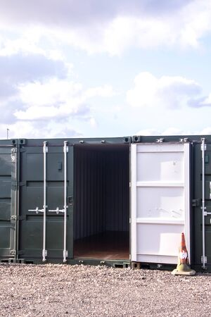 A row of storage containers with the sun setting in the background.