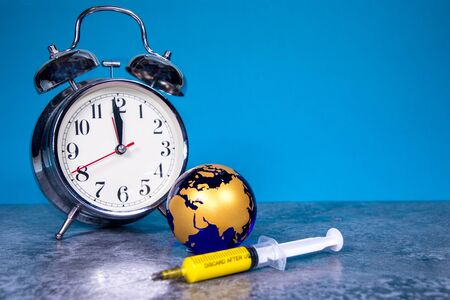 A large analogue clock counts down to a global event or depicts time running out. A syringe full of yellow medication lays infront of the planet Earth globe.