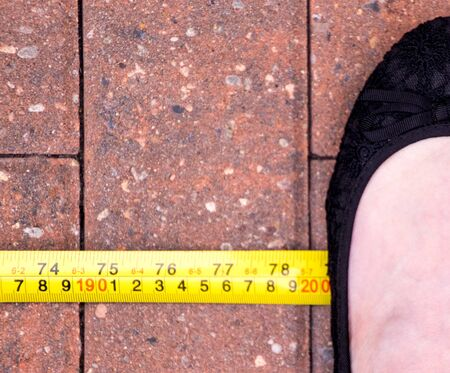 With the World in stage of a Pandemic, due to Coronavirus, the social distance advised by many countries is 2m (200cm). Here is a foot, standing at the 2 meter mark. Stock fotó