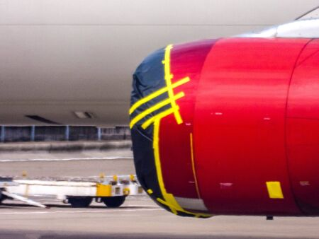 A large passenger aircraft sitting parked up with it's large engine covered up at the front and rear to protect it from any unwanted debris or visitors.