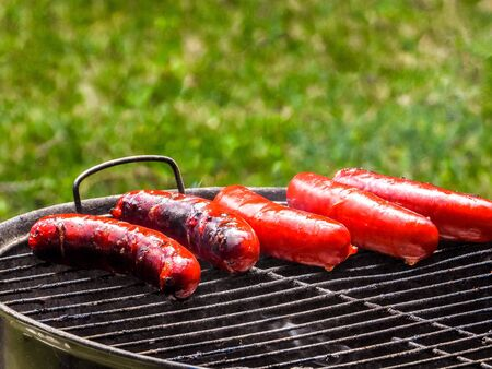 A small barbeque that has been prepared with hot coals ready and cooking delicious red sausages.