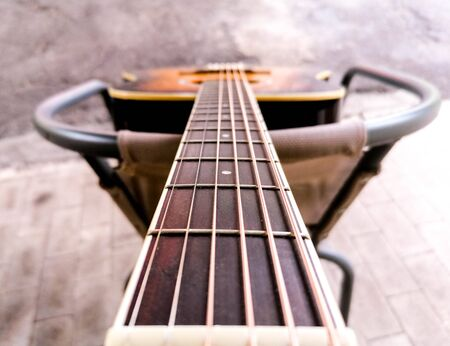 An acoustic guitar view from the top alone the strings.