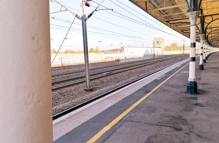 A view along a British train station platform during a sunny day. Multiple posts hold up the long platform shelter.
