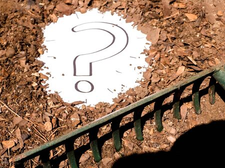 A question mark sign that has been unearthed and discovered in the earth of a garden or field. Foto de archivo