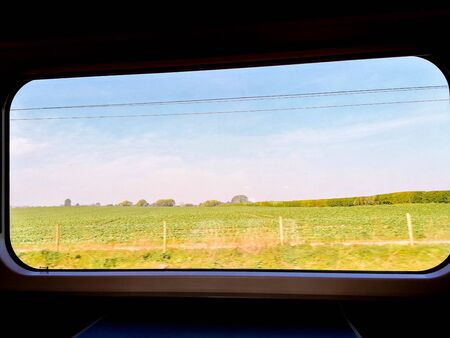 A view from a passenger window seat table as the train races through the British countryside.