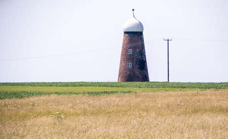 An odd shaped building in the middle of the British countryside, described as an 'Onion' shaped building. An old wind mill converted into a house.