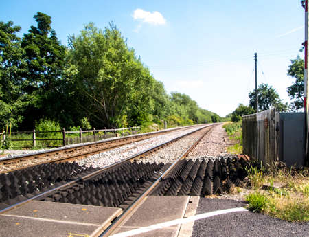A typical railway line crossing in the United Kingdom, on a dry summer's day.