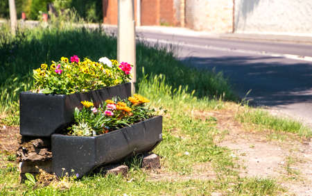 A flower pot with colorful flowers at the entry to a small town in the heart of England, UInited Kingdom.