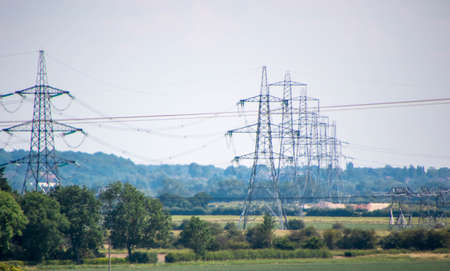 A row of electricity pylons stretch across the countryside, in the United Kingdom.