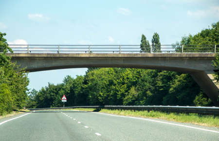 A typical British road leading under a small bridge. The road leading round to the right in the distance, being empty of other traffic. Banco de Imagens