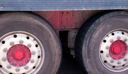A closeup of wheels in motion from an articulated lorry, traveling along a UK motorway. Banco de Imagens