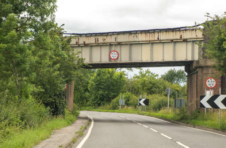 A typical British road leading under a small bridge. The road leading round to the right in the distance, being empty of other traffic. Stockfoto