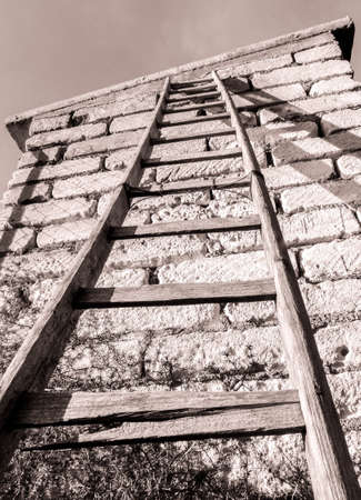 An old set of wooden ladders that have been left to decay, against a wall, in the countryside of Sicily, Italy.