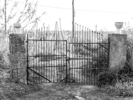 Old rusty metal farm gates with a touch of humor as someone has put 2 toilet seats as the fence posts, in Sicily, Italy.